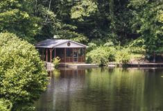 Wood Cabin on Calm Green Lake Royalty Free Stock Images