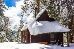 Wood Cabin With Snow On Roof. Wood Cabin On Top Of Mountain With Snow Piled On Roof royalty free stock image