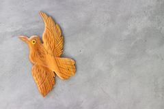 Wood carved as a bird, attached to the lofty style cement wall. Wood carved bird attached lofty style cement wall stock image