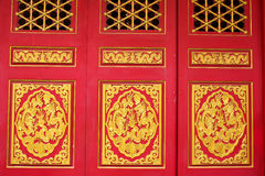 Wood carved Chinese on red doors Royalty Free Stock Photography