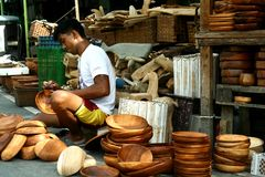 Wood carver puts finishing touches on wooden plates sold at Dapitan Arcade in Manila, Philippines Royalty Free Stock Photo