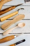 Wood carver`s instruments. And some wooden blanks on rustic wooden background royalty free stock image