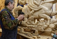 Wood carver at work. St. Petersburg, Russia - October 27, 2016: Wood carver Anatoly Zharov works on wooden decoration of the first Russian ship of the line Stock Photo