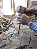Wood carving. Carver with chisel and hammer. A skillful craftsman working on a panel of wood carve decoration royalty free stock photography