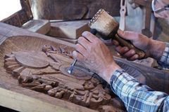 Wood carving. Carver with chisel and hammer. A skillful craftsman working on a panel of wood carve decoration stock images