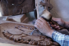 Wood carving. Carver with chisel and hammer. A skillful craftsman working on a panel of wood carve decoration royalty free stock images