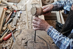 Wood carving. Carver with chisel and hammer. A skillful craftsman working on a panel of wood carve decoration royalty free stock photos