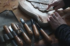 Wood carving, craftsman`s hands cut out the bas-relief, Stock Photos