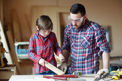 Wood carving. Father and son processing wooden plank in workshop Royalty Free Stock Photo