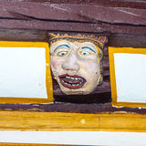 Wood carving with funny face on timber balk. Wood carving and colored on balk, timber of old framework houses Stock Photography