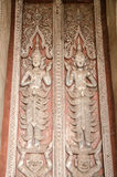 Wood Carving Pictures on the doors of Haw Phra Kaew temple at Vientiane, Laos. Delicate and elaborated detailed of the Buddhist monastery window. Ancient Laos Stock Image