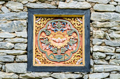 Wood carving on a rock wall Stock Photography