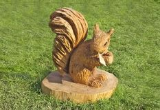 Wood carving of a squirrel with a chainsaw, hammers and. Wood carving of a squirrel with a chainsaw hammers and chisel royalty free stock image