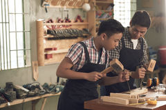 Wood carving. Vietnamese men teaching his son wood carving Stock Photo