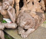 Wood carving works - lion and sitting man, Ubud. Royalty Free Stock Photo