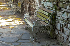 Wood and Cast iron Park Benches on Shaded Walkway Royalty Free Stock Photography