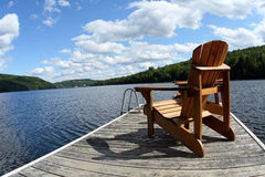 Wood chair on boat deck on the lake. A wide panoramic view of a wood made chair sitting on a boat deck on the Lake Mercier on a sunny summer day with water, sky stock photo