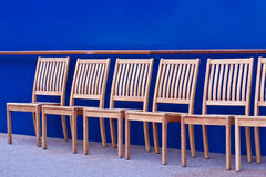 Wood Chairs in Front of Blue Wall Stock Image
