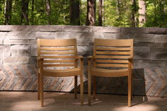 Wood Chairs on a Patio. Wooden Chairs are ready for relaxed visitors in a scenic forest setting with a stone wall in the background Stock Photography