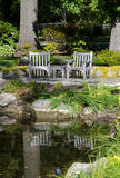 Wood chairs by a pond Stock Photography