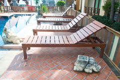 Wood chaise longues. Beside swimming pool stock photography
