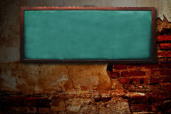 Wood chalk board on grunge wall Royalty Free Stock Image