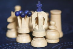 Wooden chess pieces. With the focus on the king with queen and other pieces behind him Royalty Free Stock Images