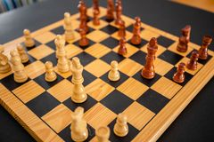 Wood chess pieces on board game. brown vintage background royalty free stock images