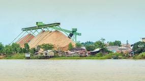 Wood chip stockpile factory on Mahakam riverbank. Industrial background stock images
