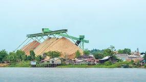Wood chip stockpile factory on Mahakam riverbank. Industrial background royalty free stock photo