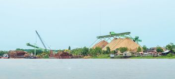 Wood chip stockpile factory on Mahakam riverbank. Industrial background royalty free stock images