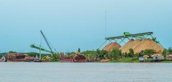 Wood chip stockpile factory on Mahakam riverbank. Industrial background stock image