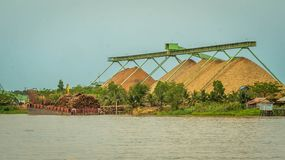 Wood chip stockpile factory on Mahakam riverbank. Industrial background stock photography