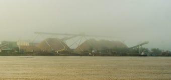 Wood chip stockpile factory on Mahakam riverbank. Wood chip stockpile on Mahakam riverbank in a misty morning, Borneo, Indonesia Royalty Free Stock Photos