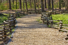 Wood Chip Trail Between Split Rail Fences. A natural trail in a forest park made of wood chips and a split rail fence stock image
