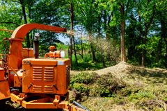 Wood Chipper in Action captures a wood chipper or mulcher shooting chips over a fence. royalty free stock images
