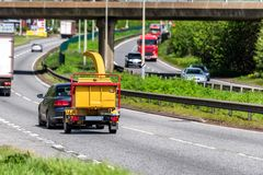 Wood chipper towed by car on uk motorway in fast motion.  stock image