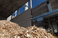 Wood chips. Pile of wood chips at biomass co-generation plant at the foreground in focus and chimneys with beautiful blue sky in the background out of focus royalty free stock photography