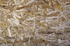 Wood chips on the natural pine plank. Derivability. The wall on the background of recycled wood chips royalty free stock photos