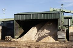 Wood chips pellets chopped wooden logs and stacked wooden pallets for biomass fuel at sawmill. Uk stock images