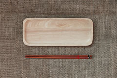 Wood chopsticks and wood tray on canvas texture. Stock Image