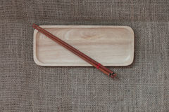 Wood chopsticks and wood tray on canvas texture. Royalty Free Stock Image