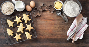 Wood Christmas Cookies Baking Banner. Christmas cookies with baking utensils, ingredients and cookie cutters on a rustic wood background from above Stock Image