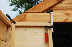 Wood Clamps on Garden Shed. Two red handled wood working clamps holding together a wall panel and a roof end of a wooden prefabricated garden shed which is under stock images