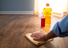 Wood cleansing and manteinance. Male hand applying wood care products on hardwood floor surface with a microfiber cloth Stock Photos