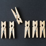 Wood clothespins in a row on a dark background Stock Images