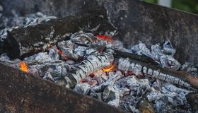 Wood coals with a flame in a Mongolian bbq royalty free stock image
