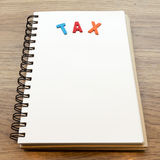Wood colorful letter word tax lay down notebook on wood backgrou. Concept of Wood colorful letter word tax lay down notebook on wood background Stock Image