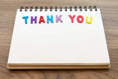 Wood colorful letter word THANK YOU lay down notebook on wood ba Stock Images