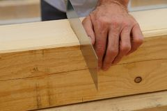 Male worker hands sawing Natural Wooden beam using saw.  detail, carpenter hands at work with a saw. royalty free stock photography